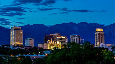 The Salt Lake City skyline by night. The city sits in a valley, with stunning mountain backdrops all around