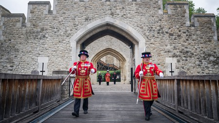Yeoman Warders, commonly known as Beefeaters, march across the Middle Drawbridge at the Tower of London