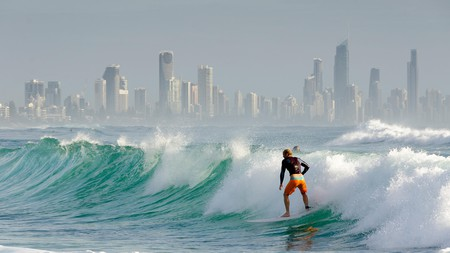 Surfers at Burleigh Heads, Tower block apartments at Surfers Paradise in distance, Queensland, Australia