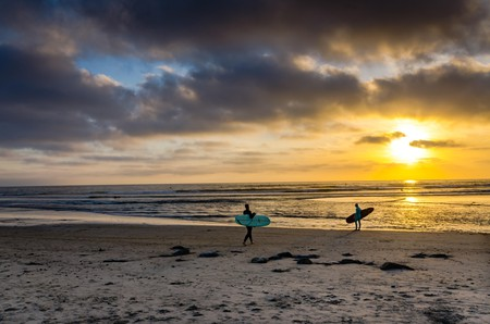 Two surfers entering the ocean at sunset at Cardiff State Beach near San Diego, California.