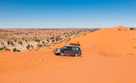a 4WD enthusiast reaching the crest of the 'Big Red' dune after crossing the Simpson Desert.