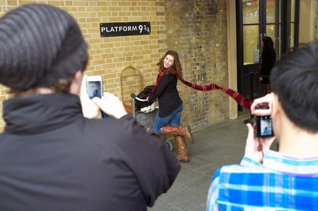 A tourist poses at the secret Platform 9 3/4, a setting in a Harry Potter film. King's Cross railway station, London, UK.