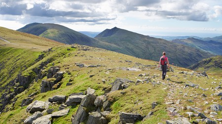 A hiker walking off Great Carrs towards the Old Man of Coniston and Dow Crag in the Lake District.