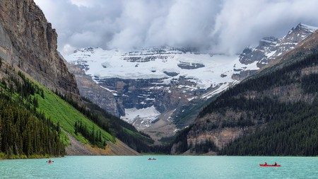 The snow-capped Rocky Mountains overlooking canoes out on Lake Louise