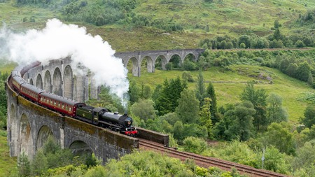 The greatest railway journey in the world: The Jacobite steam train crossing Glenfinnan Viaduct, West Highlands