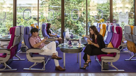 Customers sit on airplane seats as they dine at the Royal Orchid Dining Experience, a Thai Airways International pop-up restaurant
