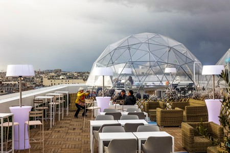 The Ice Cube bar, above Galeries Lafayette, in Paris, is just one of the city's many rooftop bars with amazing views