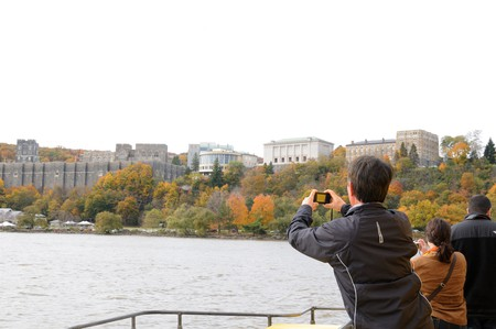 Passengers on a Hudson River fall foliage cruise take pictures as the boat passes the U.S. Military Academy at West Point.