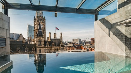 A rooftop infinity pool offers stunning city views of Manchester's Town Hall