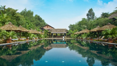 Lush gardens surround the pool at Pilgrimage Village, Hue
