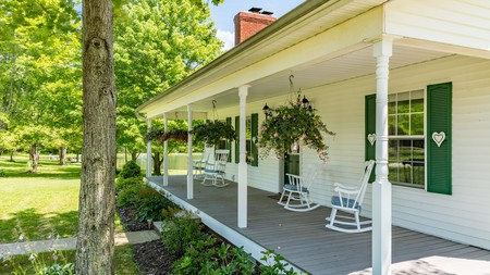 Relax on the wraparound porch of the Bear Creek Farm B&B in Kingsville, Ohio
