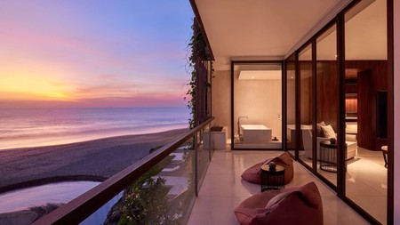A private balcony overlooks the beach at the Alila Seminyak resort