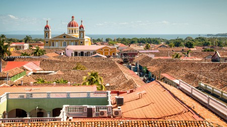 Red-tiled roofs and the mustard-yellow cathedral dominate the view of the historical center of Granada, Nicaragua
