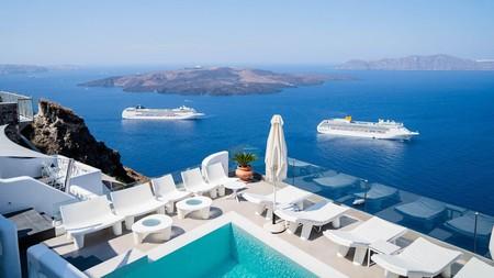 The blazing whitewashed buildings of Athina Luxury Suites on Santorini gaze out onto the azure Aegean