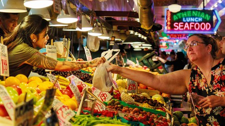Shoppers pick up fresh produce at Pike Place Market in downtown Seattle