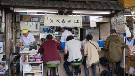 Tiny restaurant stall serving Japanese breakfast food to customers in the outer market of Tsukiji Fish Market in Tokyo.