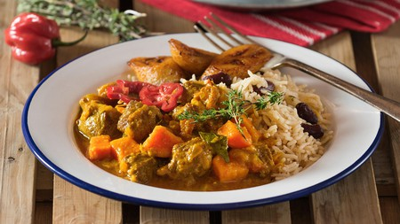 Curry goat with rice and peas is a Jamaican speciality, brimming with spices and melt-in-the-mouth, slow-cooked tender goat