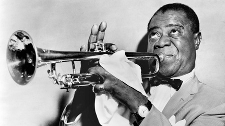 One of the founding fathers of Jazz, Louis Armstrong plays the trumpet in the 1950s