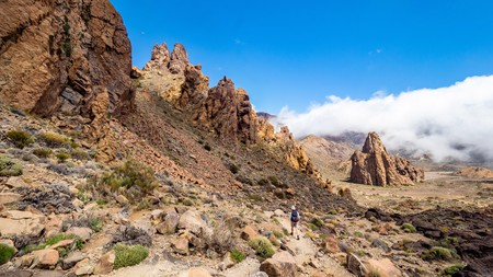Female walker approaching striking rock formation The Cathedral, Mount Teide, Tenerife.