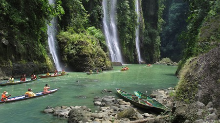 Tourists in boats snap photographs of Pagsanjan Falls on Luzon Island in the Philippines