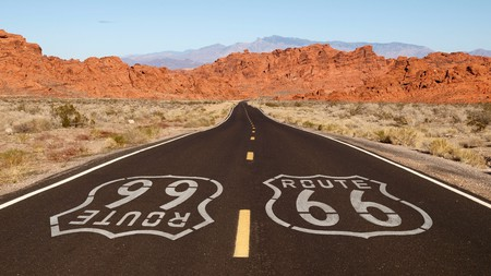 The Route 66 sign, with the red rock mountains of the Mojave desert in the background
