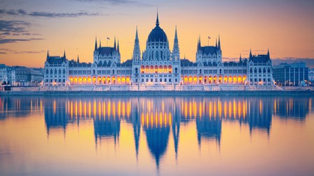 Admire the sun rising over majestic Hungarian parliament building in Budapest.