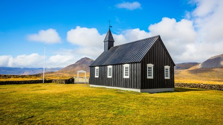 The Black Church of Budir contrasts sharply against the verdant landscape of western Iceland