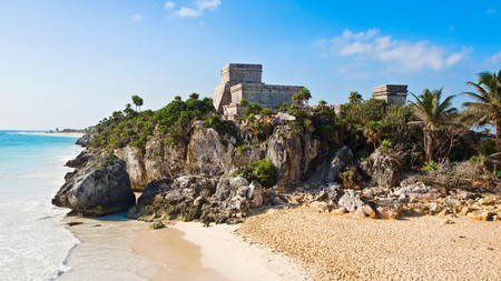 At the Tulum Archaeological Zone, ruins are dotted on the shore alongside palm trees and clear waters