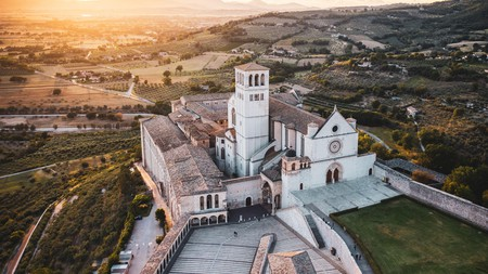 At sunset, Assisi's Basilica di San Francesco is a majestic site nestled amid rolling hills