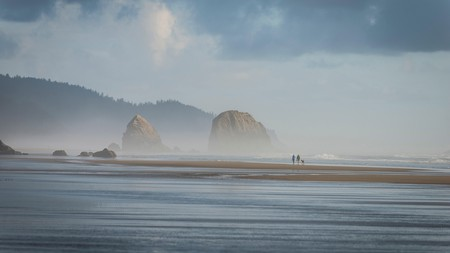 A couple walk their dog along Cannon Beach, one of Oregon's most picturesque patches of sand
