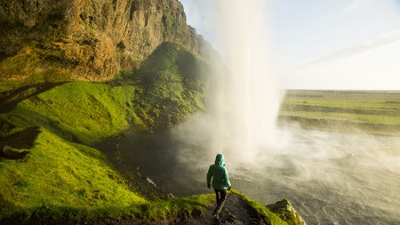 A woman watching the sunset from behind a waterfall in Iceland