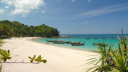 Freedom beach in Phuket Thailand with boats tied up and clear water