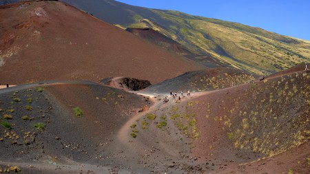 2A68E6E Tourists hiking through the volcanic landscape of The Craters Silvestri  of Mount Etna (Volcano), Sicily, Italy. 8/3/2019.