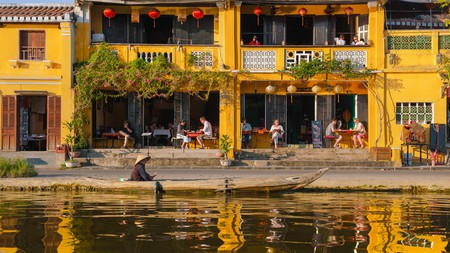 M8RNN9 Hoi An tourists Vietnam, at sunset along the Thu Bon river in the Old Town quarter of Hoi An tourists relax in a waterfront cafe bar, Vietnam.