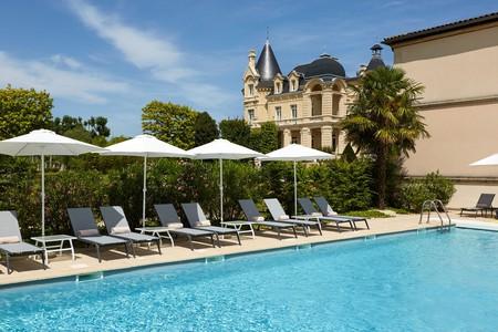 Relax poolside at the Château Hôtel Le Grand Barrail near Bordeaux, France