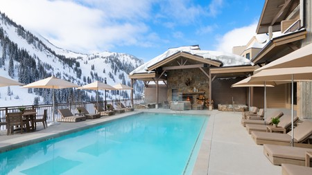 Gaze at snow-covered mountains from the pool at the Snowpine Lodge in Utah