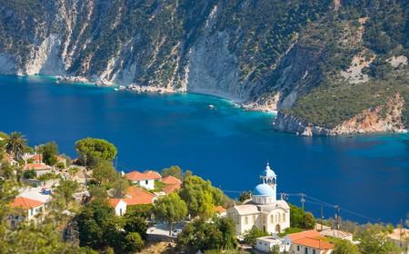 Village houses and church perched above the deep blue waters of Afales Bay, Exogi, Ithaca (aka Ithaki, Ithaka), Ionian Islands, Greece, Europe