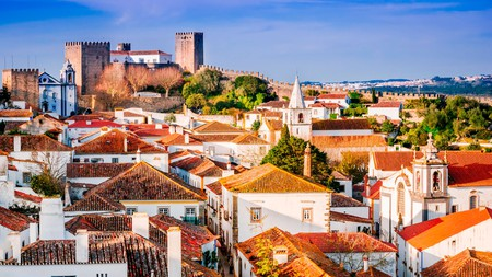 Red roofs and a Medieval castle make up the skyline of Óbidos, Portugal