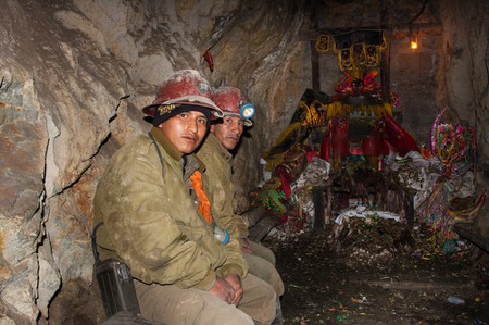 Miners pray with offerings of cigarettes, beer and coca leaves