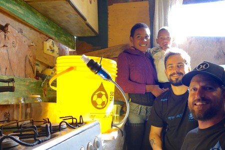 Jon Rose, Guga Ketzer and Jessica after they just gave her access to clean drinking water in favela Jardim Itapema in 2014   © Red Bull