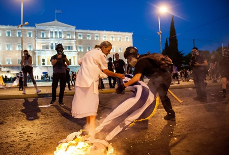 A woman attempts to stop a rioter from burning the Greek flag