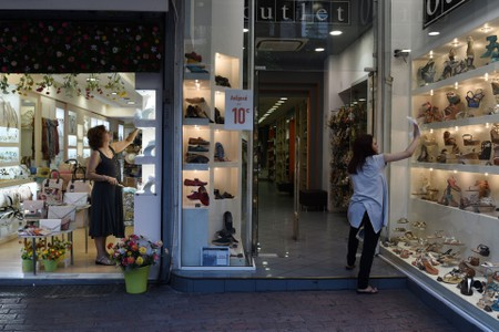 Two women clear the storefronts of their shops at Ermou Street, Athens