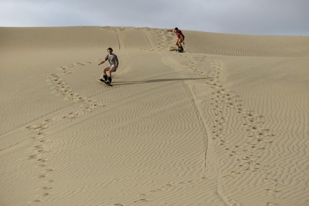 Two boarders bombing a sand mountain