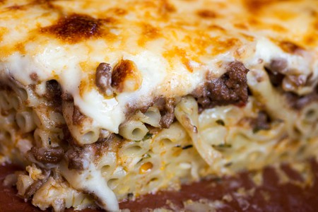 Pastitsio, traditional Greek baked pasta casserole with ground beef, tomatoes, feta cheese and bechamel sauce