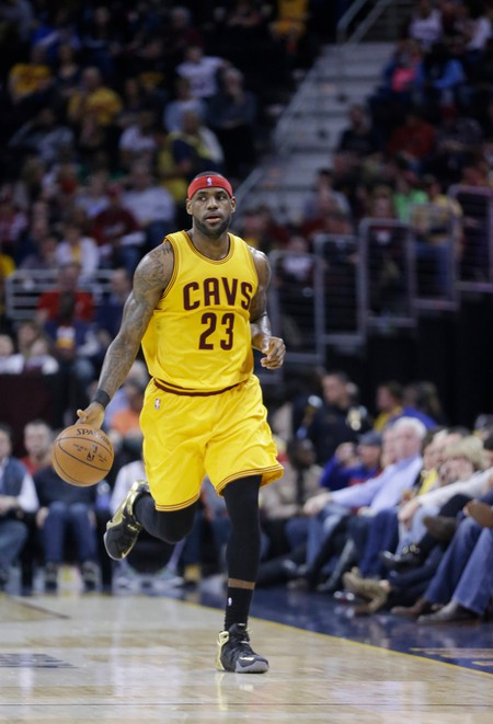 LeBron James brings the ball up against the Los Angeles Lakers in an NBA basketball game in Cleveland