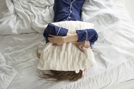 Too lazy to get out of bed, a woman covers her face with a pillow.
