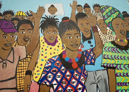 completed mural themed on the Development and Promotion of Women Leadership, depicting crowds of people supporting a female candidate,