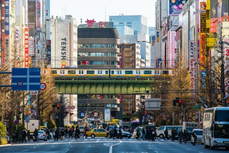 Looking down the wide street in Akihabara Electric City, Tokyo, Japan, during on busy daytime. People cross while a metro sails overhead