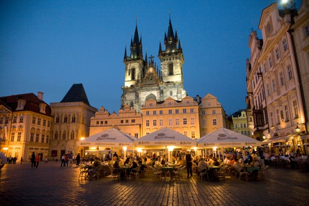 People relax outside at bars and restaurants in Prague