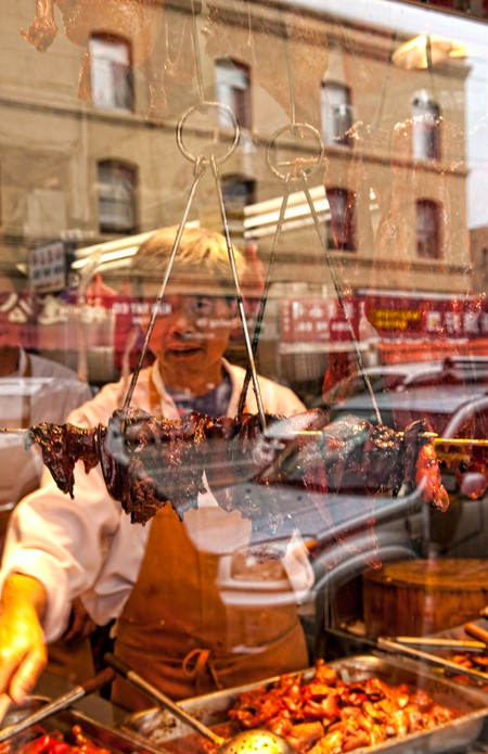 Chinese man arranging Peking Duck in window in Chinatown, San Francisco, California